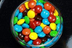 涂上巧克力用在黑背景的彩虹糖果 库存图片