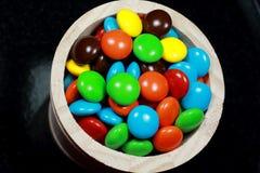 涂上巧克力用在黑背景的彩虹糖果 免版税库存照片
