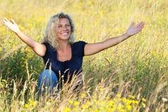涂她的胳膊的愉快的成熟妇女在草甸 图库摄影