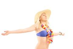 涂她的胳膊的比基尼泳装的轻松的白肤金发的女性 库存图片