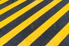 涂柏油与对角黑和黄色警告条纹的背景 免版税库存照片