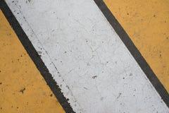 涂柏油与破裂的白色和黄色条纹的高速公路纹理 库存图片