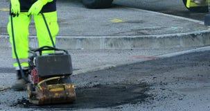 涂柏油工作者在修理与手工压紧机板材的路 股票录像