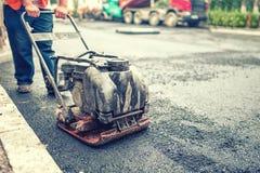 涂柏油工作者在修理的路和建筑工地 库存图片