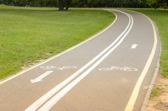涂柏油的自行车轨道在公园/涂柏油的自行车轨道在有绿草的公园 免版税库存图片