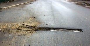 涂柏油的路的充满水的坑洼 免版税库存照片