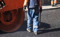 涂柏油,有一把铁锹的工作者在橙色路辗附近 库存图片