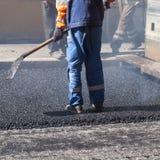 涂柏油,有一把铁锹的工作者在蓝色制服 免版税库存图片