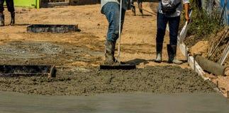 涂湿倾吐的混凝土的建筑工人 库存照片