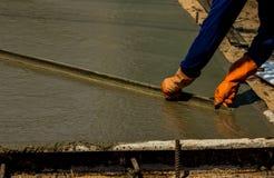 涂湿倾吐的混凝土的建筑工人 图库摄影