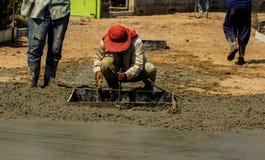涂湿倾吐的混凝土的建筑工人 库存图片
