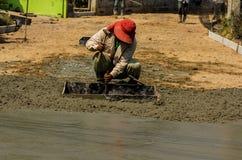涂湿倾吐的混凝土的建筑工人 免版税库存照片