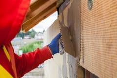 涂灰泥一个新房的门面的矿物rockwool盘区的工作者 绝缘材料房子的过程更好的节能的 库存图片