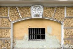 涂灰泥一头狮子的头在门面的在与格子的一个窗口上 免版税库存照片