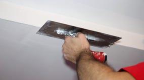 涂灰泥与工作工具的建筑工人天花板 库存照片