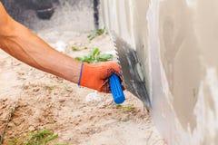 涂灰泥墙壁和房子基础与修平刀的建筑工人 库存图片