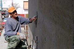 涂灰泥墙壁的人 免版税库存图片