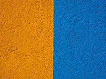 涂灰泥的门面的纹理在黄色两种的颜色的蓝色和 库存图片