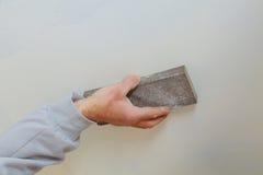 涂灰泥铺沙在干式墙缝石膏板的人手plaste 库存照片