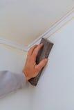 涂灰泥铺沙在干式墙缝石膏板的人手plaste 免版税图库摄影