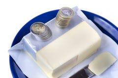 涂黄油在有欧元硬币金钱的蓝色板材在白色 免版税库存图片