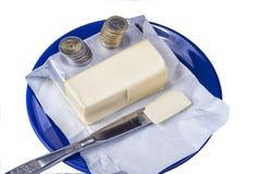 涂黄油在有欧元硬币金钱的蓝色板材在白色 库存图片