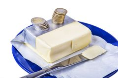 涂黄油在有欧元硬币金钱的蓝色板材在白色 免版税库存照片