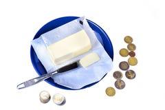 涂黄油在有欧元硬币金钱的蓝色板材在白色 库存照片