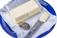 涂黄油在有欧元硬币金钱的蓝色板材在白色 图库摄影