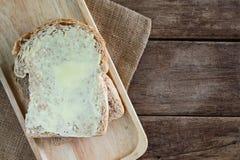 涂黄油在木板材的被堆积的切片全麦三明治面包在木桌上 免版税库存图片