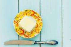 涂黄油与在葡萄酒木头背景的牛油刀 免版税库存图片