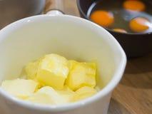 涂黄油在whte罐和卵黄质鸡蛋在木桌上 库存图片