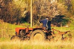涅任,乌克兰- 2017年4月21日:拖拉机在秋天的犁地球播种冬麦 侧视图 免版税库存图片