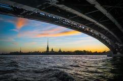 涅瓦河的彼得和保罗堡垒在日落视图的晚上从桥梁下面在微明下在圣彼德堡 免版税库存照片