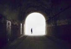 消失入光的一个人的剪影在隧道尽头 免版税库存图片