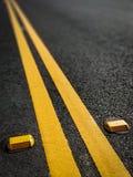 消失入距离的双重黄色交通分切器 免版税库存图片
