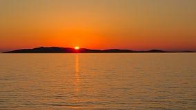 消失在一个海岛后的太阳在有海岛o的剪影的亚得里亚海天际 库存照片