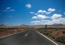 消失在天际的柏油路通过火山山山坡 雷达标志 蓝色覆盖天空白色 兰萨罗特岛 免版税库存图片