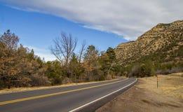 消失在岩石附近的高速公路 免版税库存照片