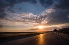 消失对天际的路在太阳下发出光线下来低谷剧烈的风雨如磐的云彩 在山路的日落 Azerbaija 免版税库存图片
