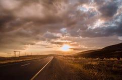消失对天际的路在太阳下发出光线下来低谷剧烈的风雨如磐的云彩 在山路的日落 Azerbaija 库存照片
