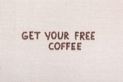 消息得到您的免费咖啡写与咖啡豆,被排列在中心 免版税库存照片