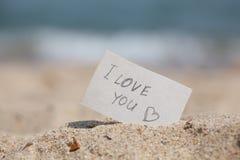 消息我爱你在沙子 库存照片