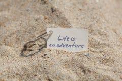 消息生活是在沙子的一次冒险 免版税图库摄影