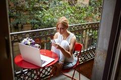 读消息的年轻可爱的妇女在她的手机,当坐在与便携式的便携式计算机时的桌上 图库摄影