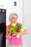 消极妇女举行未加工的新鲜蔬菜 免版税库存照片