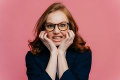 消极感觉的概念 不满意的红头发人兴旺的女实业家握紧从激怒的牙,保留手在下巴下, 免版税库存图片
