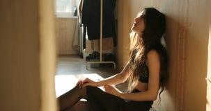 消沉概念 有长的黑发的年轻女人坐在女用贴身内衣裤和哭喊的地板 影视素材