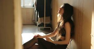 消沉概念 有长的黑发的年轻女人坐在女用贴身内衣裤和哭喊的地板 股票录像