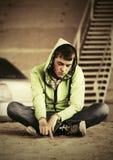 消沉的哀伤的青少年的男孩坐地面 免版税库存图片